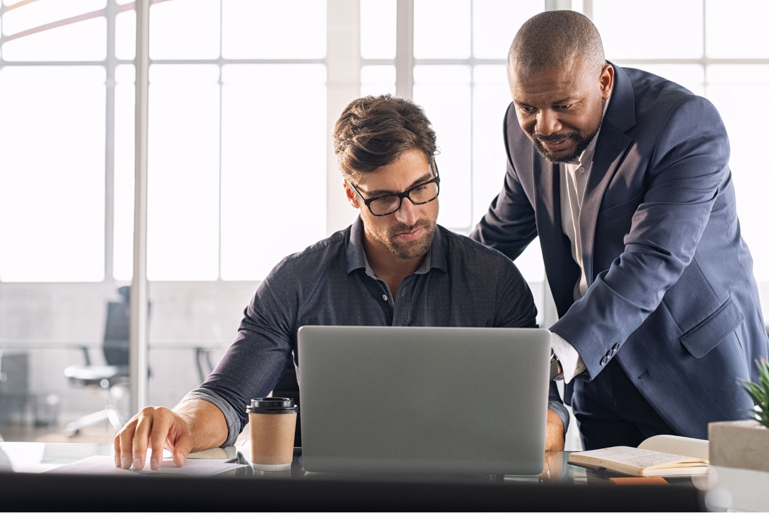 Two Men looking at improving workforce management on a laptop